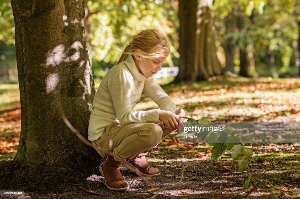 Schöne junge blonde Mädchen spielen in den Bäumen im Herbst Park : Stock-Foto