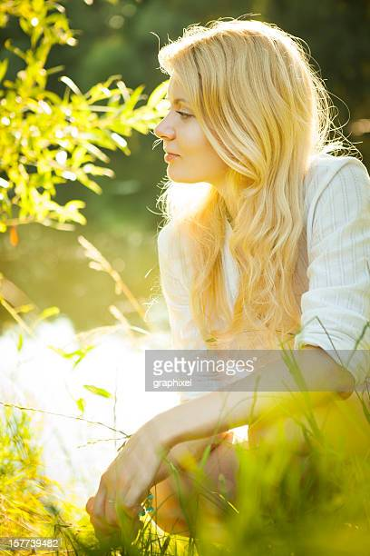 beautiful young blond woman sitting on nature - graphixel stock pictures, royalty-free photos & images