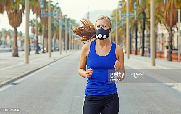 beautiful young blonde athletic female running in daytime sunny surroundings - face guard sport stock pictures, royalty-free photos & images