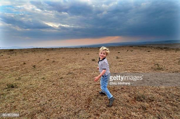 beautiful young blonde boy walking on a dry grassy field with a beautiful sky. - menino loiro olhos azuis imagens e fotografias de stock