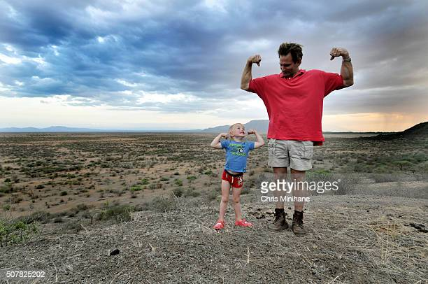 Beautiful young blonde boy with his father flexing muscles in front of a beautiful sky.