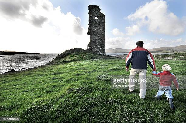 Beautiful young blonde boy with his father running across a green field towards a ruined castle.
