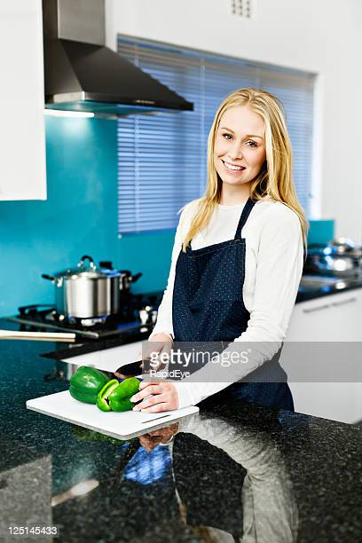Beautiful young blonde cooking in upmarket kitchen with granite counter