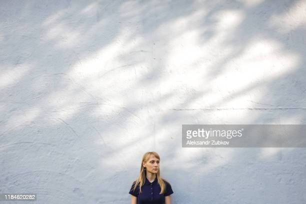 beautiful young blonde woman in blue polo shirt standing at white stone wall outdoors. a serious girl with long hair looks away, having a calm and serious expression. copy space for text. - copy space imagens e fotografias de stock