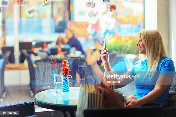Beautiful young blonde woman selfie in the cafe