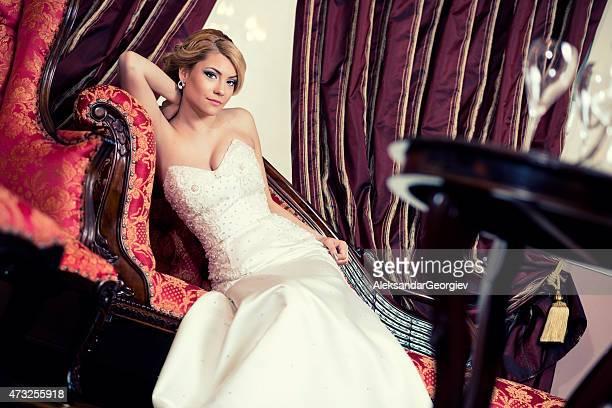 美しい若い花嫁に横たわるソファーにバロック様式のインテリア