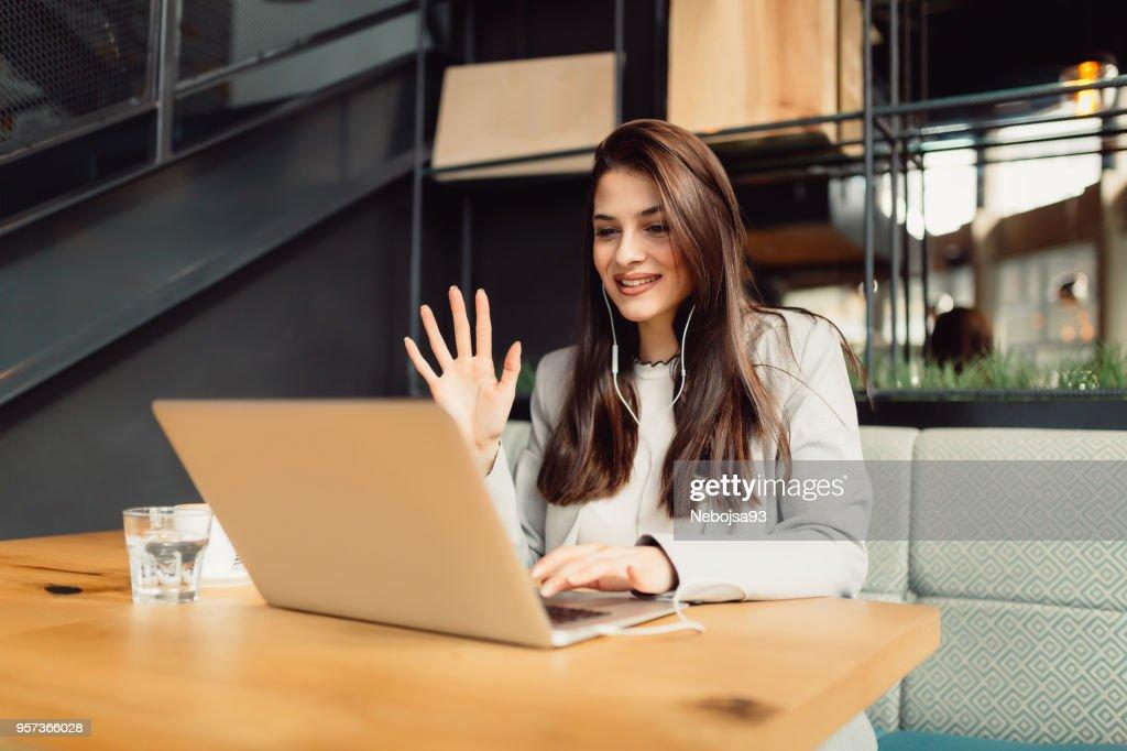 Schöne junge Brünette ist Skype-Anruf auf ihrem Laptop haben, beim Sitzen im café : Stock-Foto