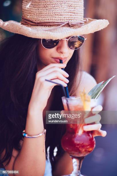 Beautiful young brunette woman drinking cocktails at summer bar