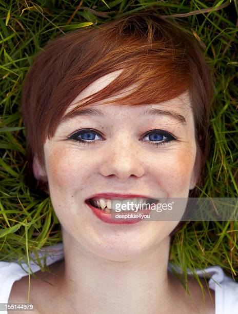 Beautiful young brunette woman head on grass portrait