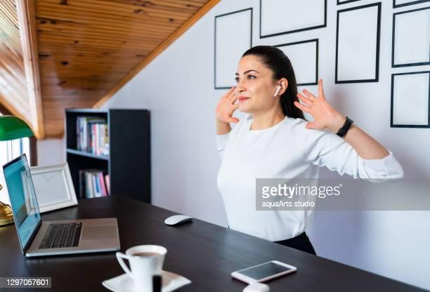 美しい若いビジネスウーマンは、自宅のオフィスでヨガのエクササイズや練習をしています。 - 息を止める ストックフォトと画像