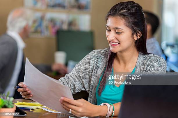 Beautiful young business woman reviews documents