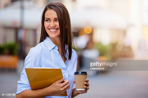 beautiful young business woman smiling and holding documents and - jeunes filles photos et images de collection