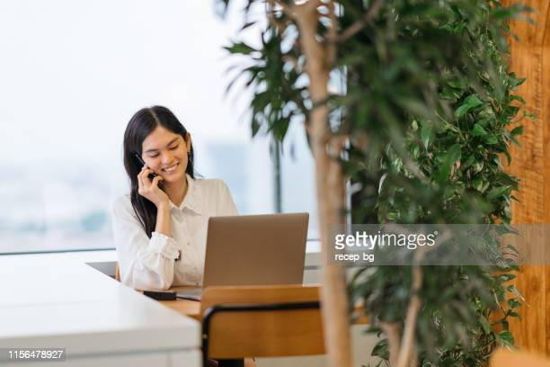 beautiful young business woman talking on phone - philippines stock pictures, royalty-free photos & images