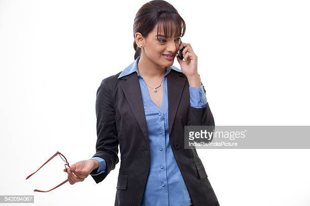 Beautiful young business woman using mobile phone on white background
