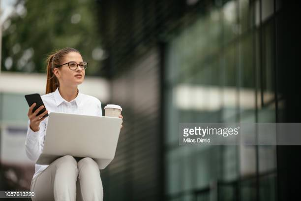 beautiful young business woman using phone and drinking coffee - social grace stock pictures, royalty-free photos & images