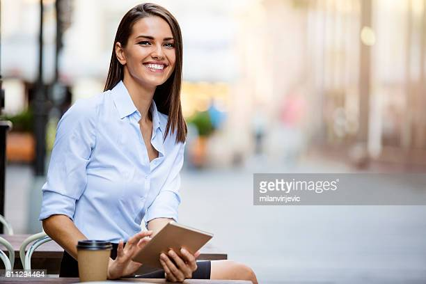 Beautiful young business woman using tablet