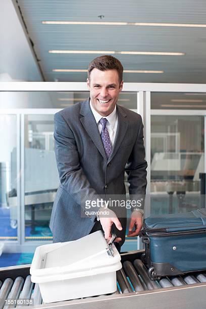 Schöne junge Geschäftsmann lächelnd am Flughafen Sicherheit