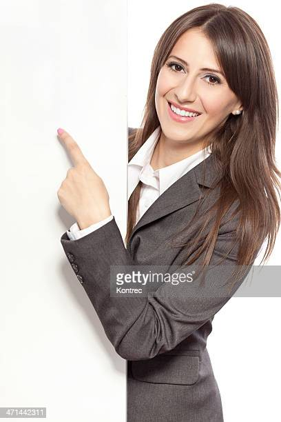 Beautiful young businesswoman pointing at copy space