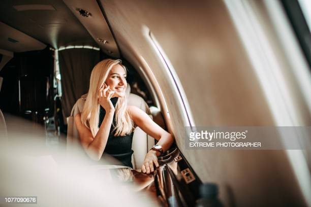 Beautiful young businesswoman talking on a mobile phone while traveling in a private airplane