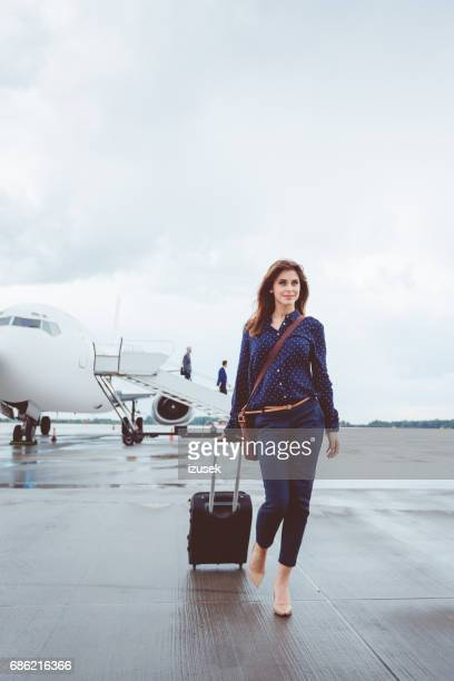Beautiful young businesswoman walking in front of airplane