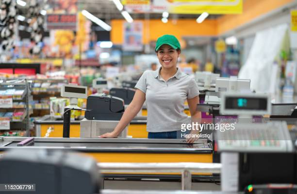 beautiful young cashier facing camera smiling ready to work - cash register stock pictures, royalty-free photos & images