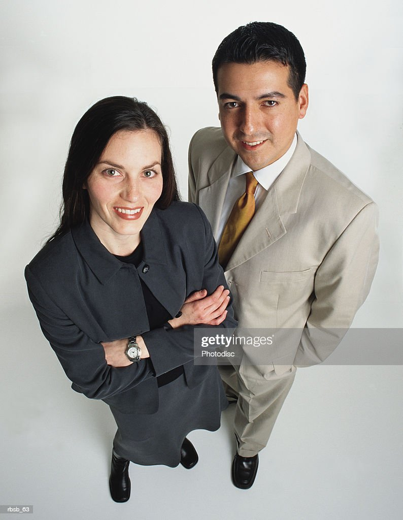 beautiful young caucasian businesswoman black hair handsome young businessman light tan suit stand : Stockfoto