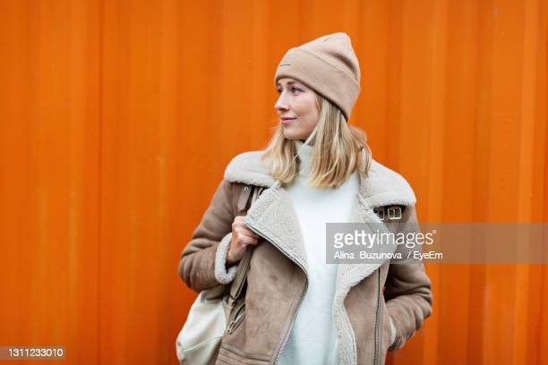 beautiful young caucasian woman 30 years old in casual clothing near orange container wall. student - 30 34 years stock-fotos und bilder