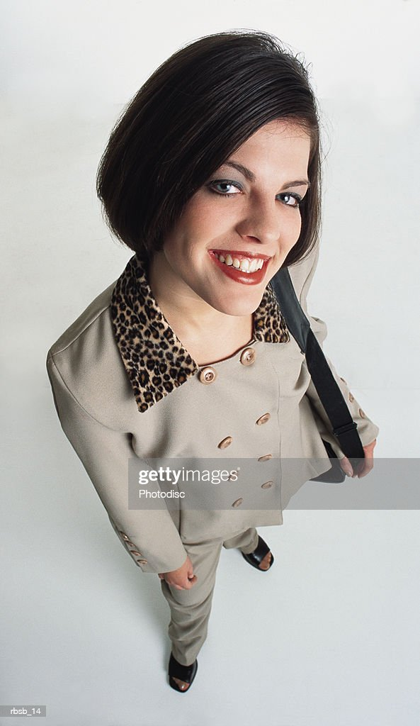 beautiful young caucasian woman with short dark hair dressed in a tan coat with  leopard collar and black purse stands looking into the camera : Foto de stock