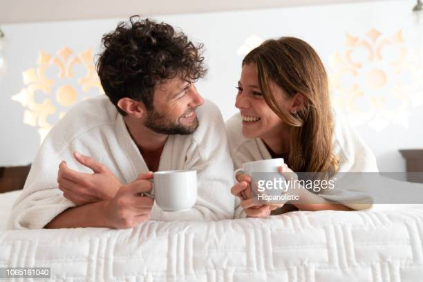 Beautiful young couple at home relaxing on bed wearing bathrobes and drinking a cup of coffee