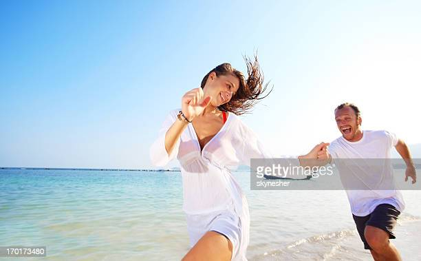 Beautiful young couple chasing at the beach