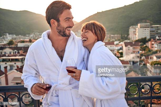 beautiful young couple chatting and enjoying together - bathrobe stock pictures, royalty-free photos & images