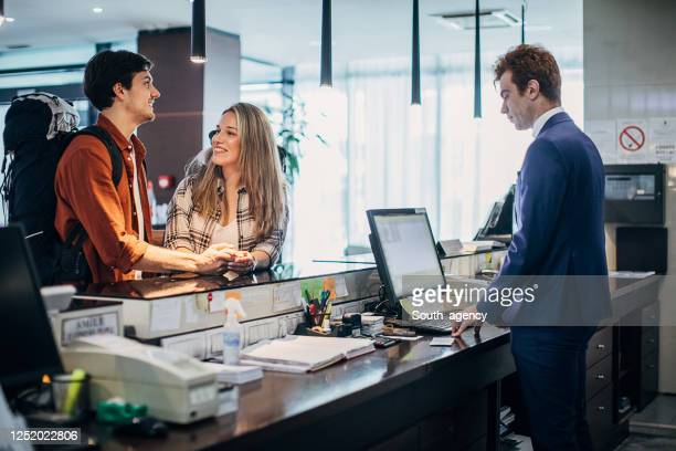 beautiful young couple doing the check-in at a hotel reception - guest stock pictures, royalty-free photos & images