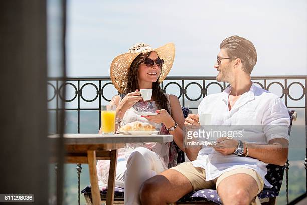 beautiful young couple having their morning coffee at the terrac - terrassenfeld stock-fotos und bilder