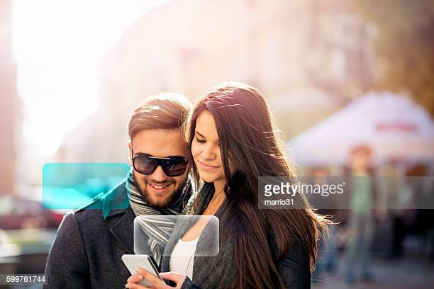 Beautiful young couple in casual clothes texting