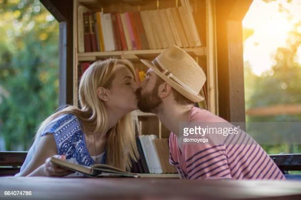 美しい若いカップルが公共図書館のキス