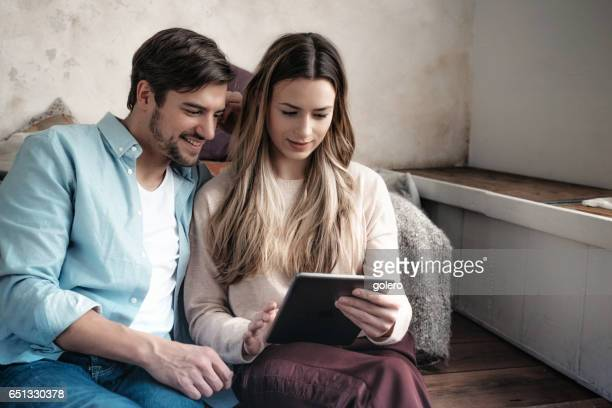 beautiful young couple looking together at tablet home