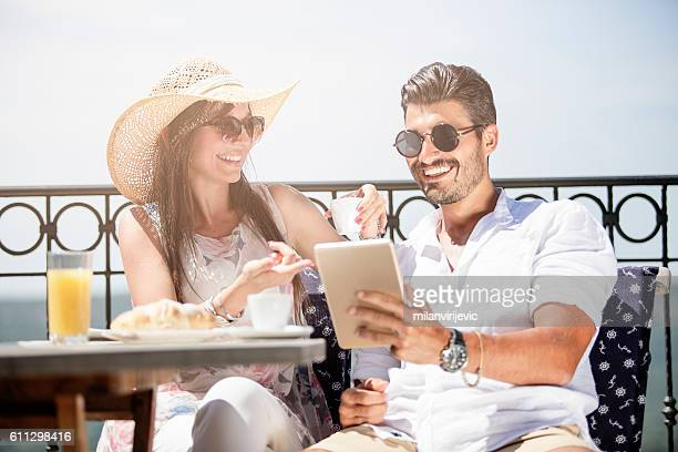 beautiful young couple reading the news at tablet - terrassenfeld stock-fotos und bilder