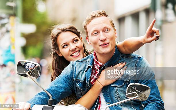 Beautiful young couple riding on a motorbike.