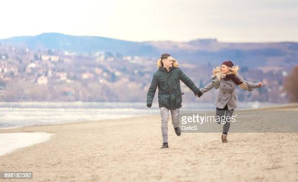 Beautiful young couple running next to the river.
