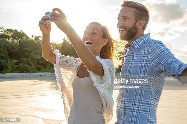 Beautiful young couple take selfie on beach using mobile phone