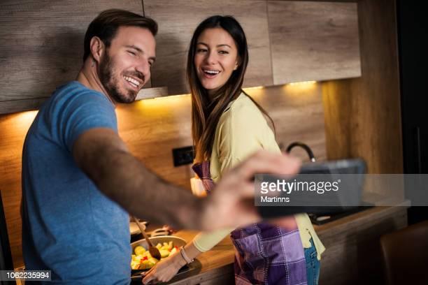 mooie jonge paar nemen van een selfie tijdens het samen koken - naughty valentine stockfoto's en -beelden