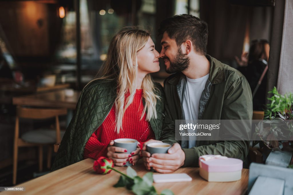 Beautiful young couple touching noses and smiling at cafe : Stock Photo