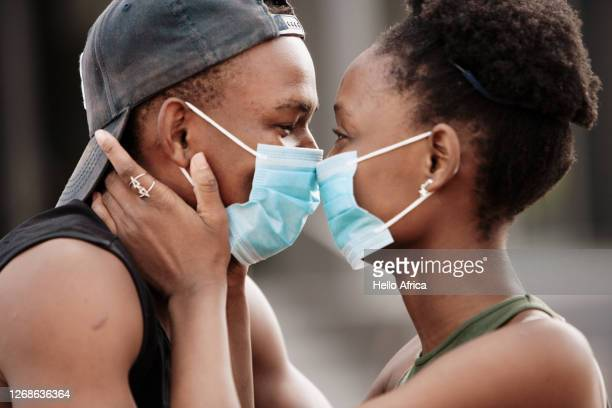 beautiful young couple wearing surgical face masks at close range - 愛 ストックフォトと画像