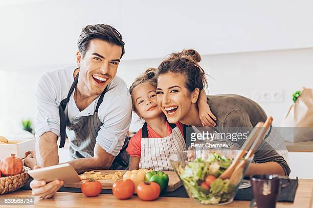beautiful young couple with small girl in the kitchen - cozinha doméstica imagens e fotografias de stock
