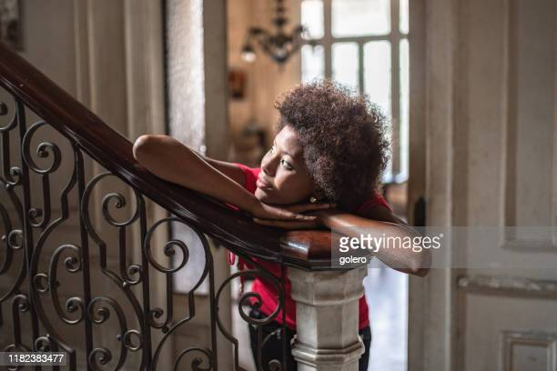 beautiful young cuban woman leaning on balustrade indoors - afro caribbean ethnicity stock pictures, royalty-free photos & images