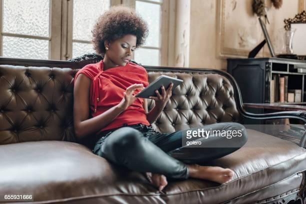 schöne junge kubanische Frau sitzt auf dem Sofa mit tablet