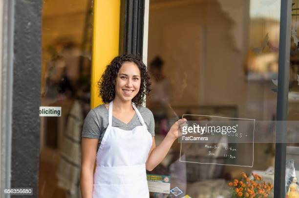 Beautiful young entrepreneur and owner standing outside her store