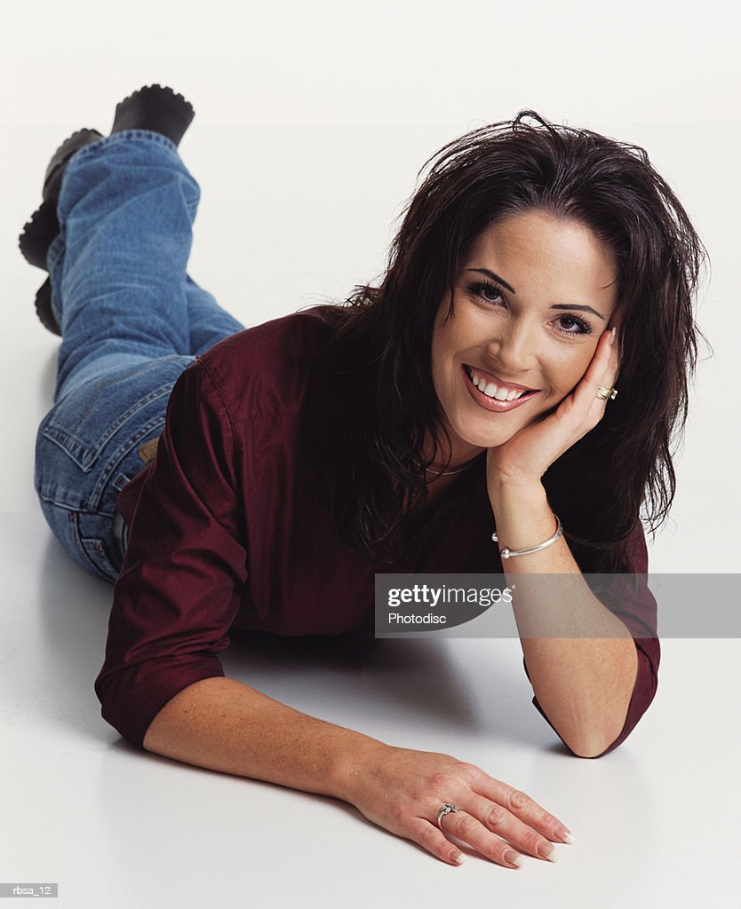 beautiful young ethnic adult female wearing a silk burgundy blouse lies on the floor while leaning her head on her hand and smiling playfully up at the camera : Foto de stock