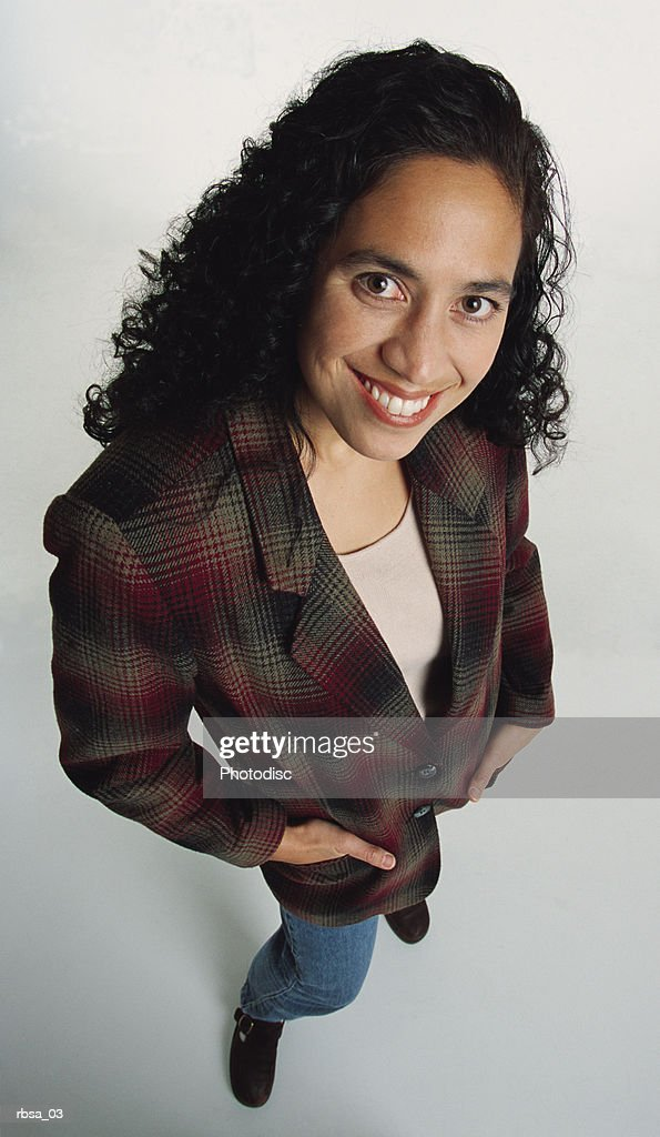 beautiful young ethnic adult female with long dark curly hair wearing a checked blazer stands and looks up at the camera while smiling approvingly : Foto de stock