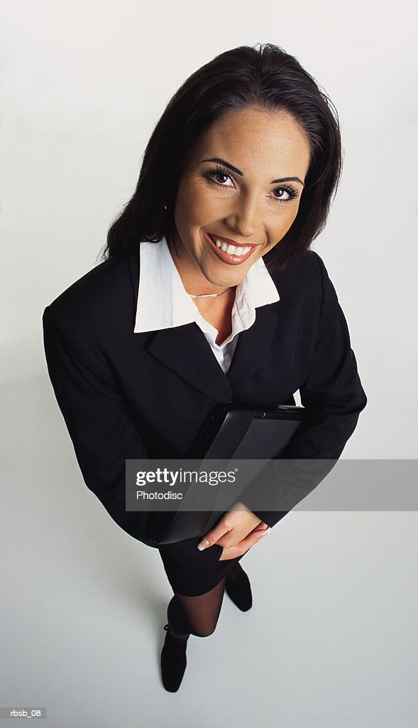 beautiful young ethnic business woman with long dark hair looks up at the camera while holding a laptop computer : Foto de stock